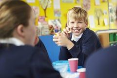 Schulkinder, die bei Tisch sitzen, Lunchpaket essend Stockbilder