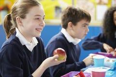 Schulkinder, die bei Tisch sitzen, Lunchpaket essend Stockbild