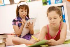 Schulkinder, die in Broschüre schreiben Lizenzfreies Stockfoto