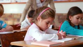 Schulkinder, die in den Büchern im Klassenzimmer färben stock footage