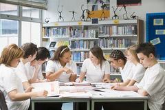 Schulkinder, die in der Schulebibliothek studieren Stockfotografie