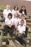 Schulkinder, die draußen auf Bänke sitzen Lizenzfreie Stockbilder