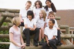 Schulkinder, die draußen auf Bänke sitzen Stockbild