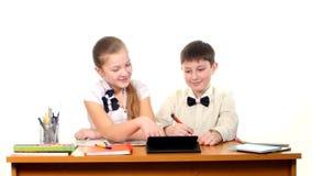 Schulkinder, die durch die Tabelle und das Handeln sitzen stock footage