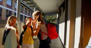 Schulkinder, die einen traurigen Jungen im Korridor der Volksschule 4k einsch?chtern stock video footage