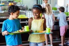 Schulkinder, die Essenstablett in der Kantine halten stockfoto