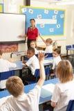 Schulkinder, die im Klassenzimmer mit Lehrer studieren Stockbild
