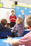Schulkinder, die im Klassenzimmer mit Lehrer studieren Lizenzfreie Stockfotos