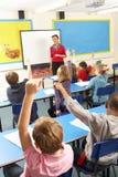 Schulkinder, die im Klassenzimmer mit Lehrer studieren Lizenzfreies Stockbild