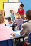 Schulkinder, die im Klassenzimmer mit Lehrer studieren Stockfotos