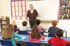 Schulkinder, die im Klassenzimmer mit Lehrer studieren Lizenzfreies Stockfoto
