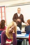 Schulkinder, die im Klassenzimmer mit Lehrer studieren Stockbilder