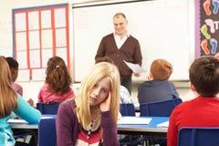 Schulkinder, die im Klassenzimmer mit Lehrer studieren Stockfotografie