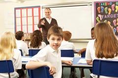 Schulkinder, die im Klassenzimmer studieren stockbilder