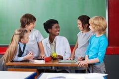 Schulkinder, die Lehrer Sitting At Desk schauen Stockfoto