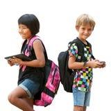 Schulkinder, die mit Tablette und Smartphone stehen. Stockbilder