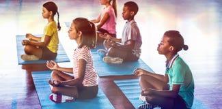 Schulkinder, die während der Yogaklasse meditieren stockfoto