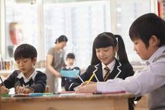 Schulkinder, die während des Kunstunterrichts, Peking zeichnen Stockbild