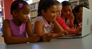 Schulkinder, die zusammen bei Tisch auf Laptop 4k studieren stock video