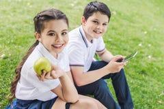 Schulkinder, die zusammen Smartphone beim Sitzen auf Gras und dem Schauen verwenden stockfotos