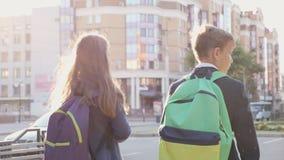 Schulkinder gehen entlang die Stadtstraße stock footage