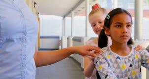 Schulkinder mit dem Lehrer, der in der Schule in der Reihe mit ihren Händen auf Schulter im Korridor 4k steht stock video footage