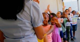 Schulkinder mit dem Lehrer, der in der Schule in der Reihe mit ihren H?nden auf Schulter im Korridor 4k steht stock video footage