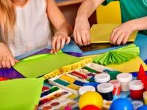 Schulkinder mit Scheren in den Kindern übergibt Ausschnittpapier Stockbild