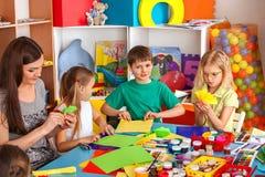 Schulkinder mit Scheren in den Kindern übergibt Ausschnittpapier Lizenzfreies Stockfoto