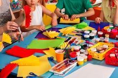 Schulkinder mit Scheren in den Kindern übergibt Ausschnittpapier Lizenzfreie Stockfotos
