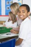 Schulkinder und ihr Lehrer in einer Kunstkategorie Stockfotos