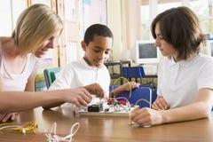 Schulkinder und ihre leanring Wissenschaft des Lehrers Stockbild