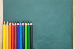 Schulkonzept-farbbleistift auf Tafelhintergrund stockbild