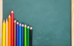 Schulkonzept-farbbleistift auf Tafelhintergrund Stockfotografie