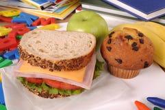 Schullunchpaket, -sandwich, -kuchen, -banane und -apfel auf Klassenzimmerschreibtisch Stockfoto
