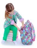 Schulmädchen überprüft einen Rucksack Stockfotos