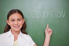Schulmädchen, das auf ein Wort zeigt Lizenzfreie Stockfotografie