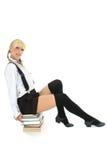 Schulmädchen, das auf gestapelten Büchern sitzt Stockfoto
