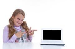 Schulmädchen, das auf ihr netbook zeigt Stockbild