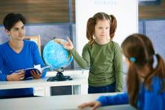 Schulmädchen, das auf Kugel zeigt Stockbild
