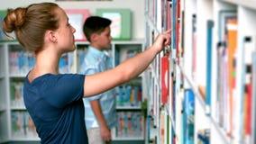 Schulmädchen, das Buch vom Buchregal in der Bibliothek vorwählt stock footage