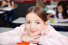 Schulmädchen, das Chin On Hands In Classroom stillsteht lizenzfreies stockbild