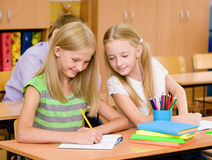 Schulmädchen, das an der Prüfung, das Schreiben eines Freunds betrachtend betrügt Stockbild