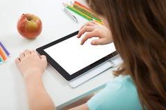 Schulmädchen, das digitale Tablette mit leerem Bildschirm verwendet Stockfotografie