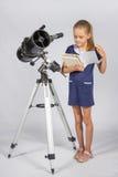 Schulmädchen, das durch ein Lehrbuch bei der Stellung am Teleskop Blätter treibt lizenzfreies stockfoto