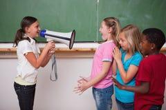 Schulmädchen, das durch ein Megaphon zu ihren Mitschülern schreit Stockfotografie