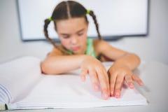 Schulmädchen, das ein Blindenschrift-Buch im Klassenzimmer liest Stockbild