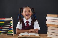 Schulmädchen, das ein Buch gegen Tafel liest Stockfotografie