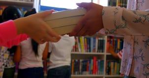Schulmädchen, das einem weiblichen Lehrer in der Schulbibliothek 4k ein Buch gibt stock footage