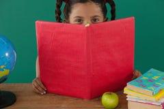 Schulmädchen, das hinter einem Buch gegen grünen Hintergrund sich versteckt Stockfoto